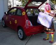 Silly Jilly the Clown loads up her red Fiat 500 with her magic suitcase.
